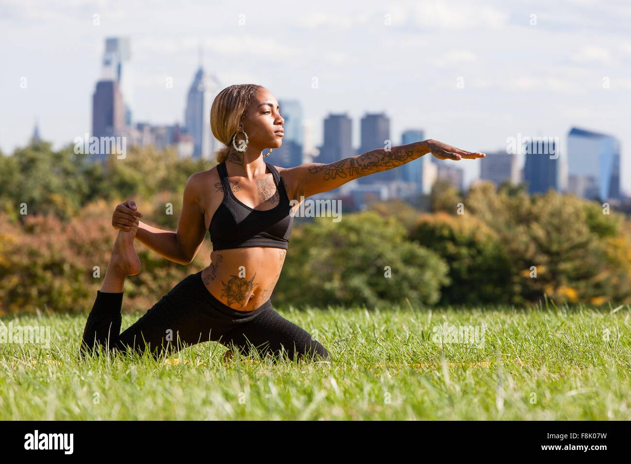 Front view of young woman kneeling on grass stretching leg in yoga position, arm out, looking away, Philadelphia, - Stock Image
