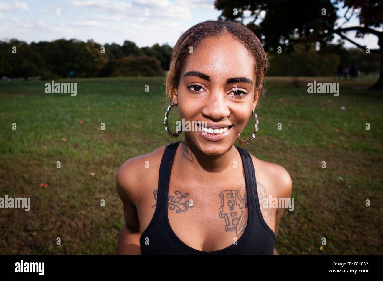 Young tattooed woman wearing crop top and hoop earrings, looking at camera smiling - Stock Image
