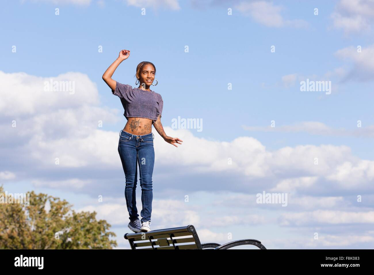 Young woman wearing crop top balancing on back on park bench - Stock Image