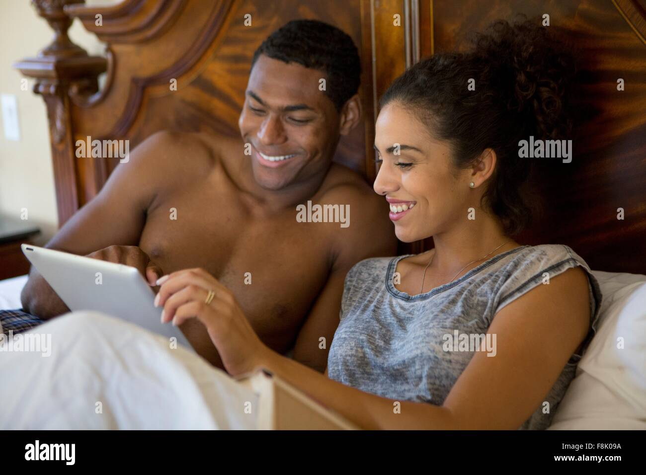 Couple in bed using digital tablet smiling - Stock Image
