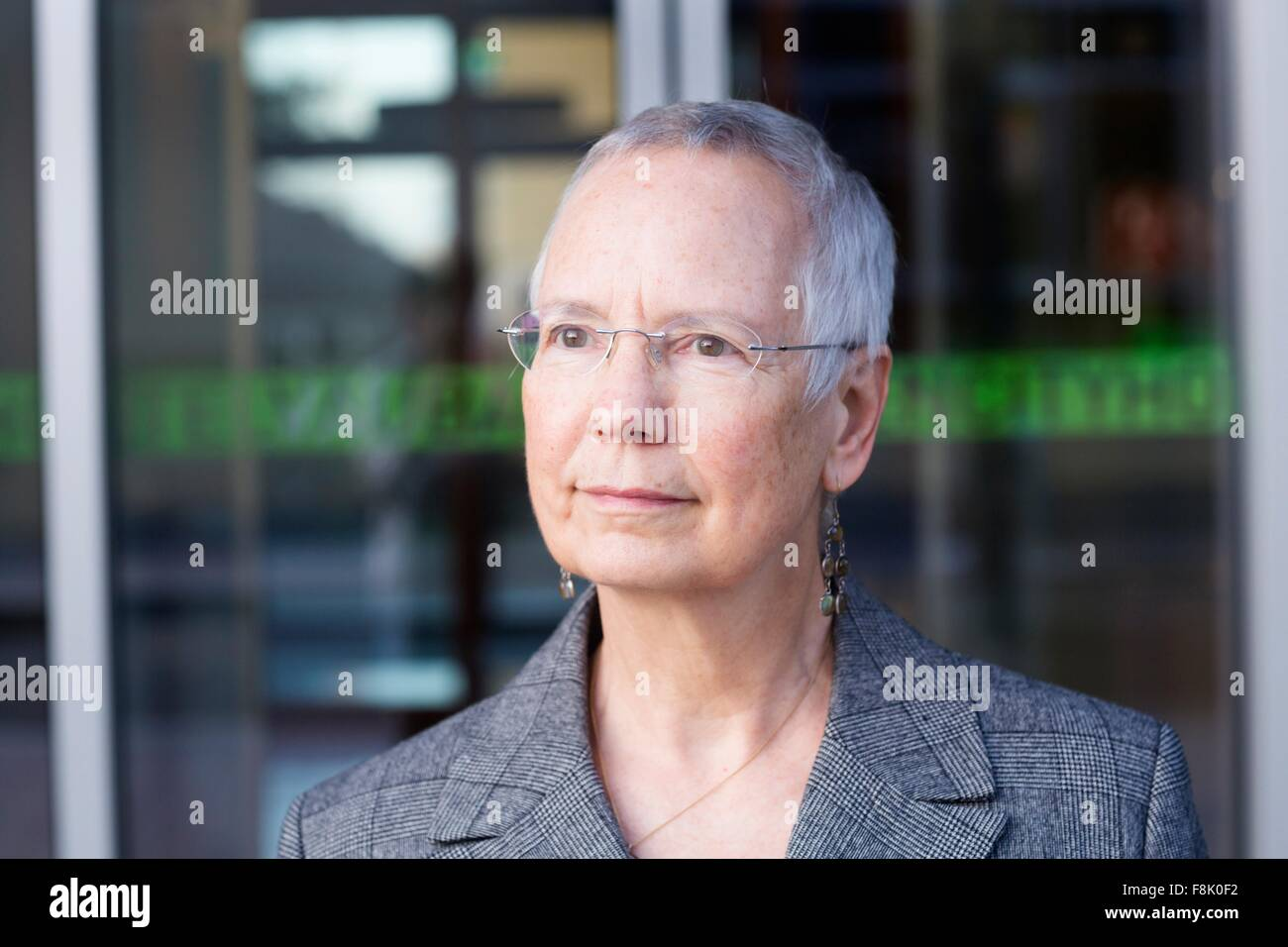 Portrait of senior businesswoman with short grey hair outside hotel entrance - Stock Image