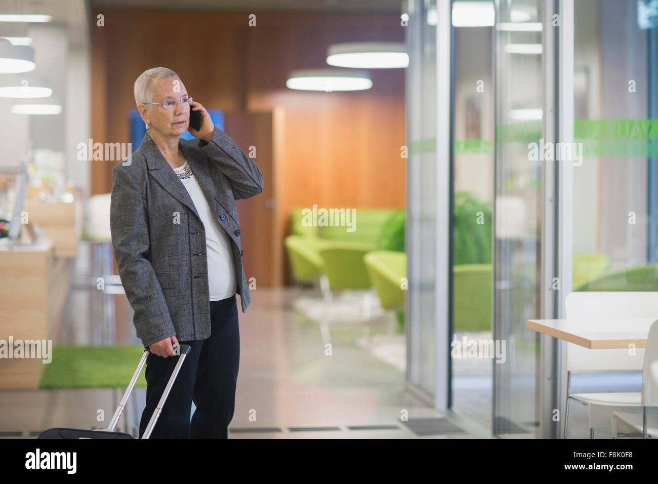 Senior businesswoman with wheeled suitcase chatting on smartphone in hotel lobby - Stock Image