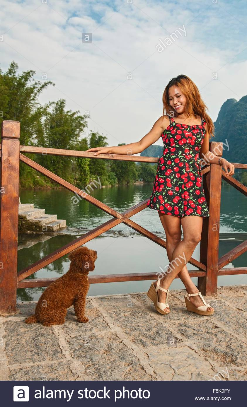 Portrait of young woman and obedient poodle at Li river, Yangshuo, Guangxi Zhuang, China - Stock Image