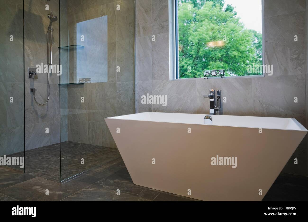 Modern bathroom with free standing bath tub and glass fronted shower cubicle - Stock Image