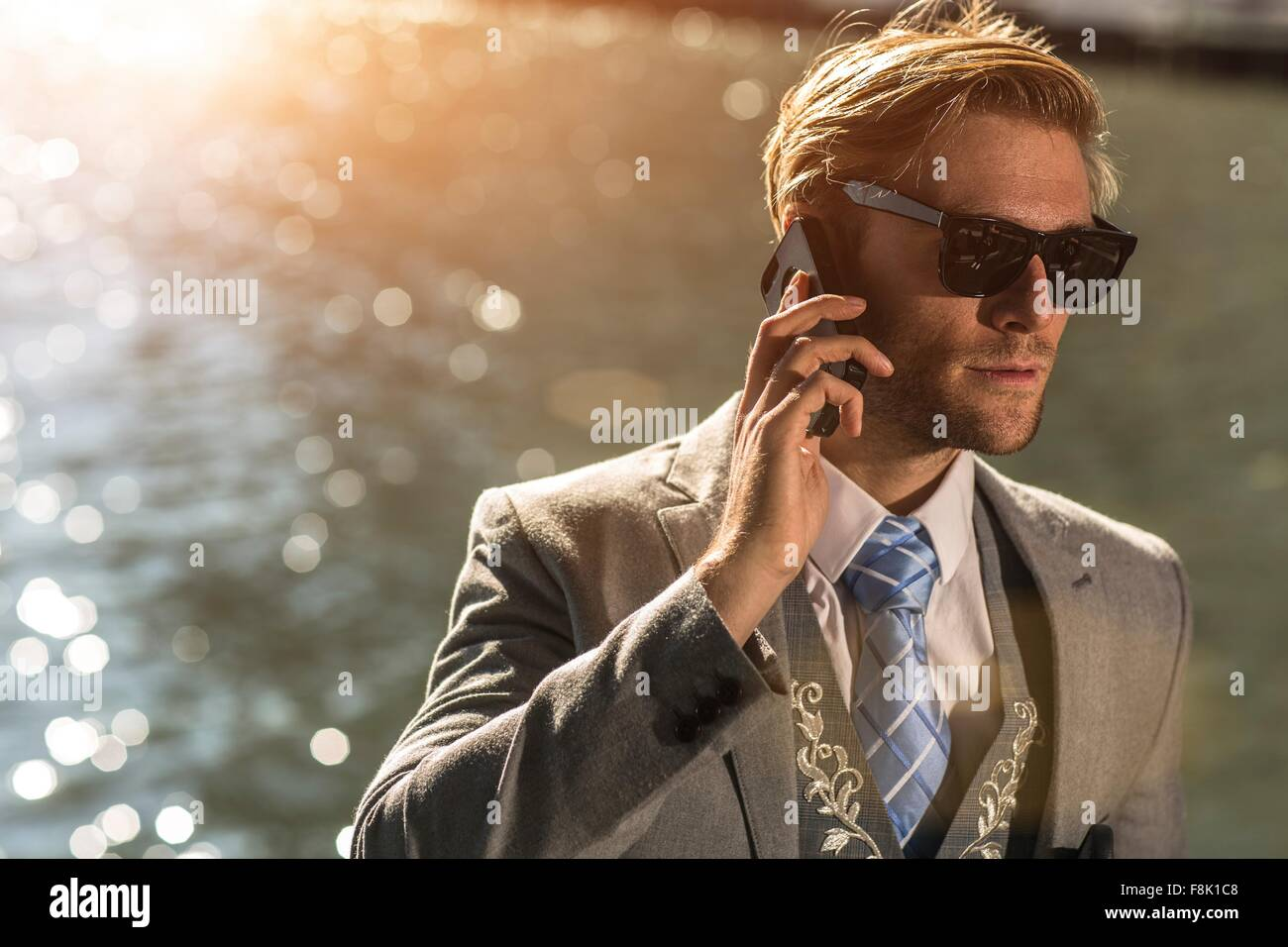 Young businessman wearing sunglasses talking on smartphone on waterfront - Stock Image