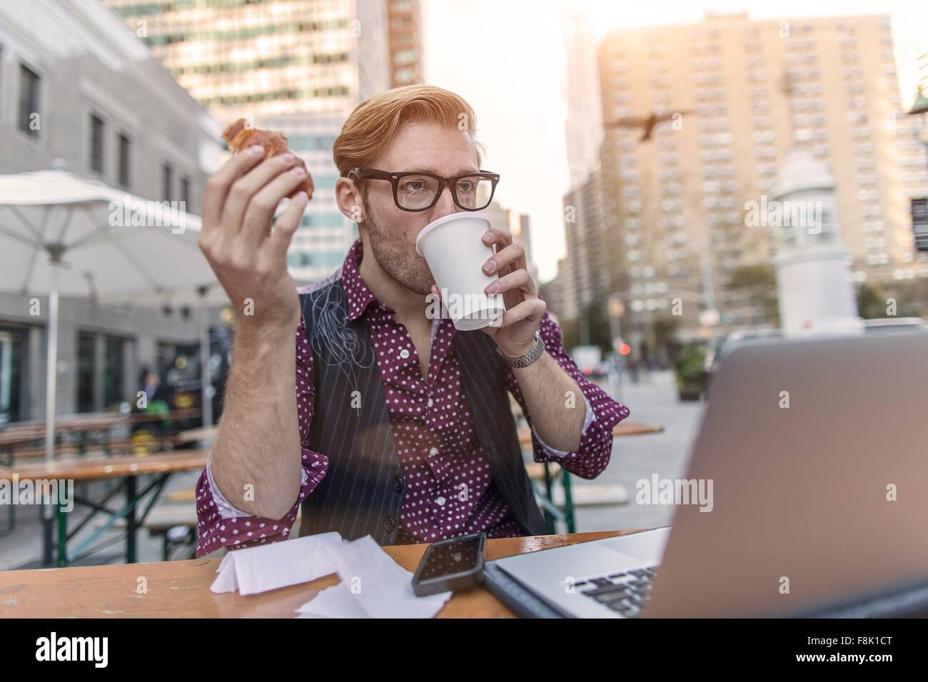 Stressed young businessman hurrying working lunch at sidewalk cafe, New York, USA - Stock Image