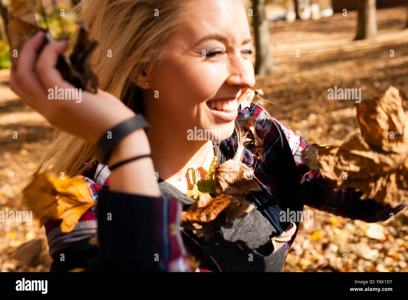 Young woman throwing autumn leaves in forest - Stock Image