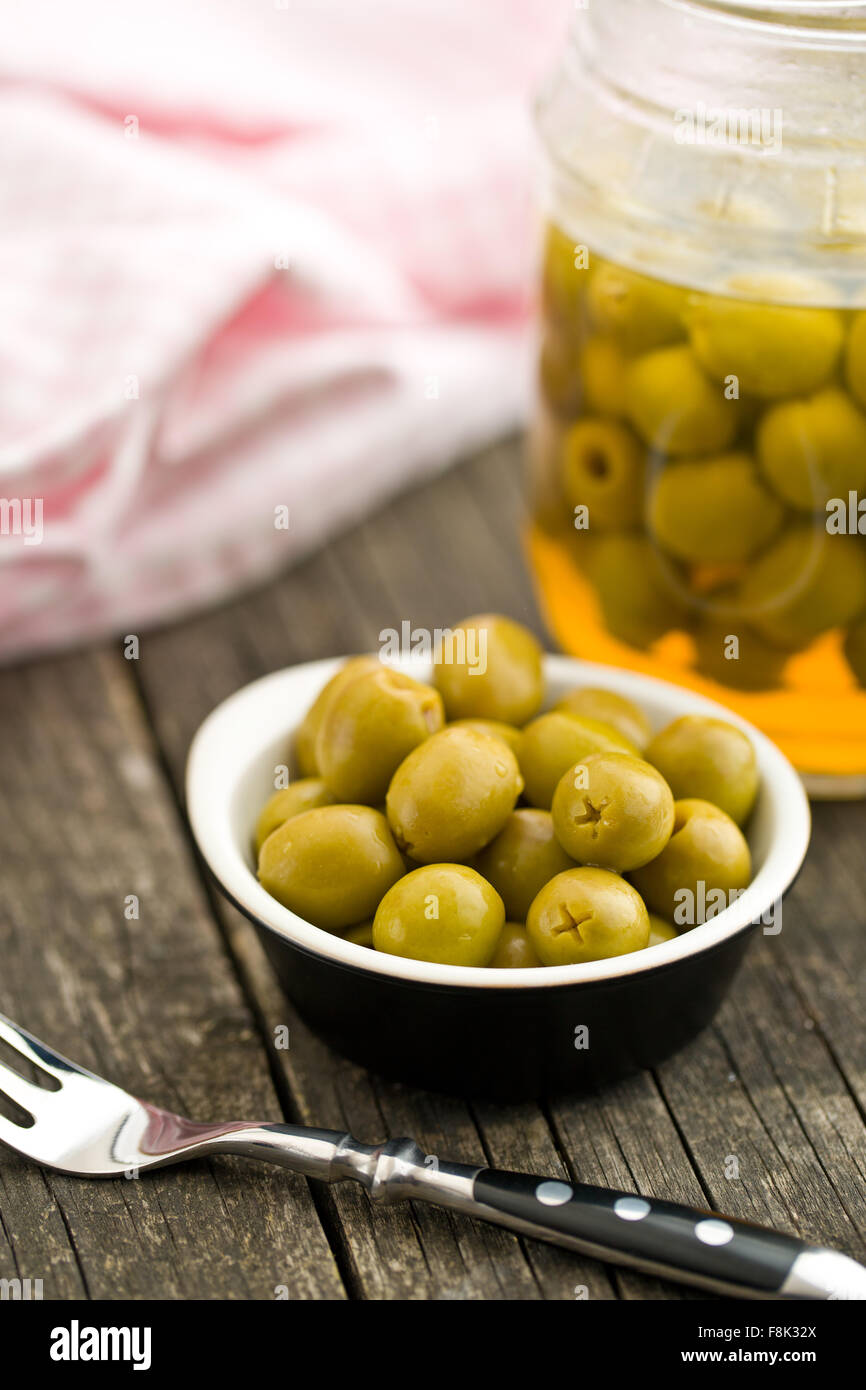 pitted green olives in bowl on wooden table - Stock Image