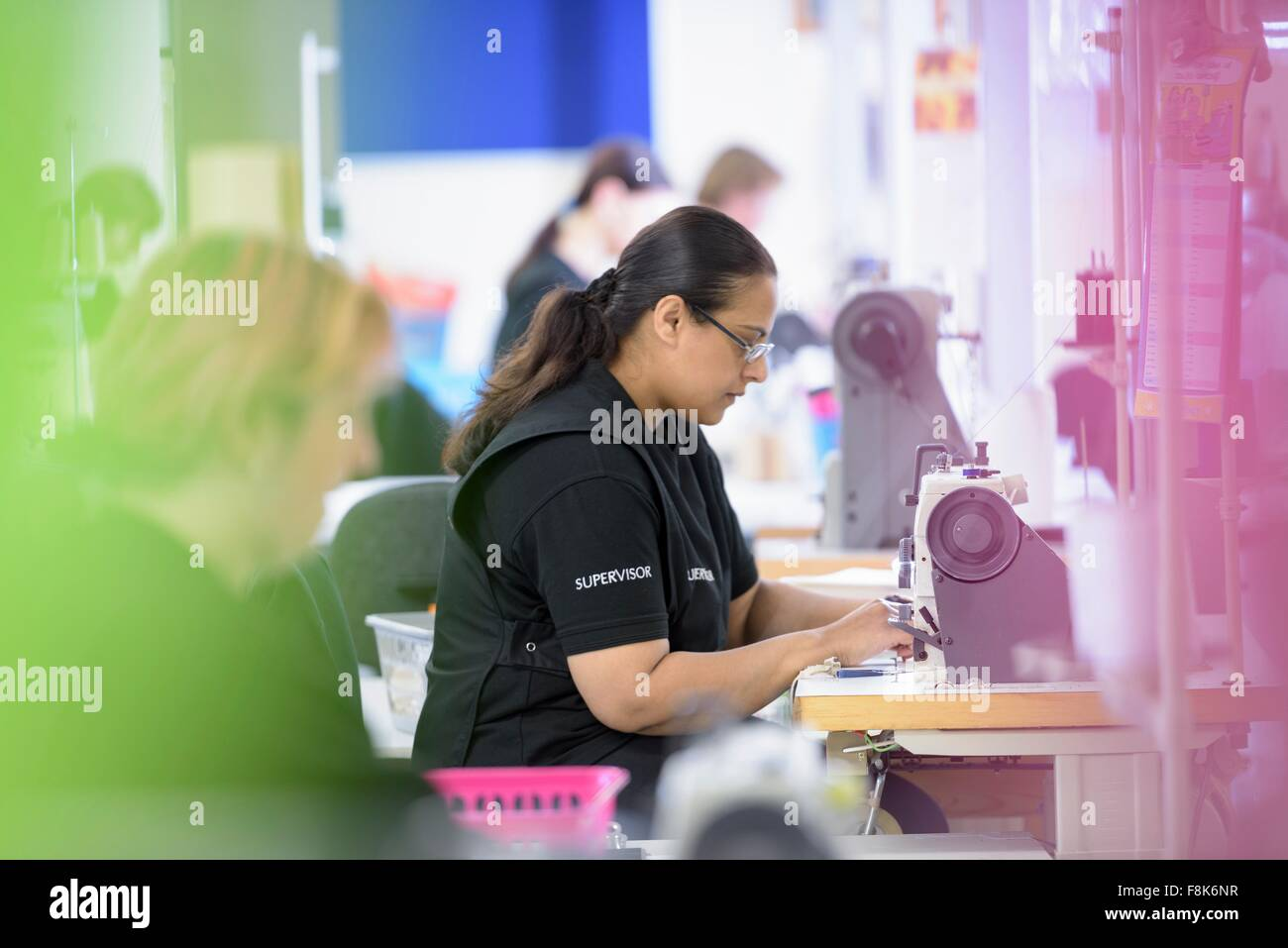 Workers sewing orthopaedic garments in factory - Stock Image