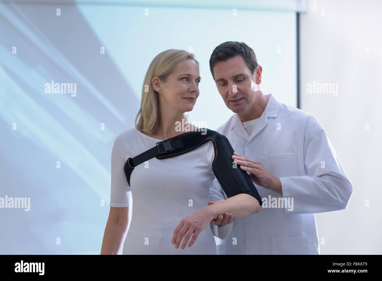 Doctor fitting orthopaedic sling to patient - Stock Image