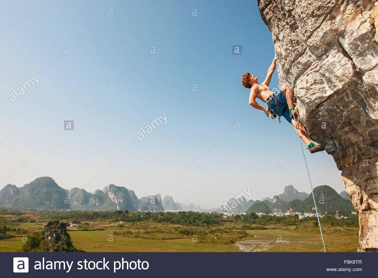 Male climber climbing on the Egg - a limestone cliff in Yangshuo, Guangxi Zhuang, China Stock Photo
