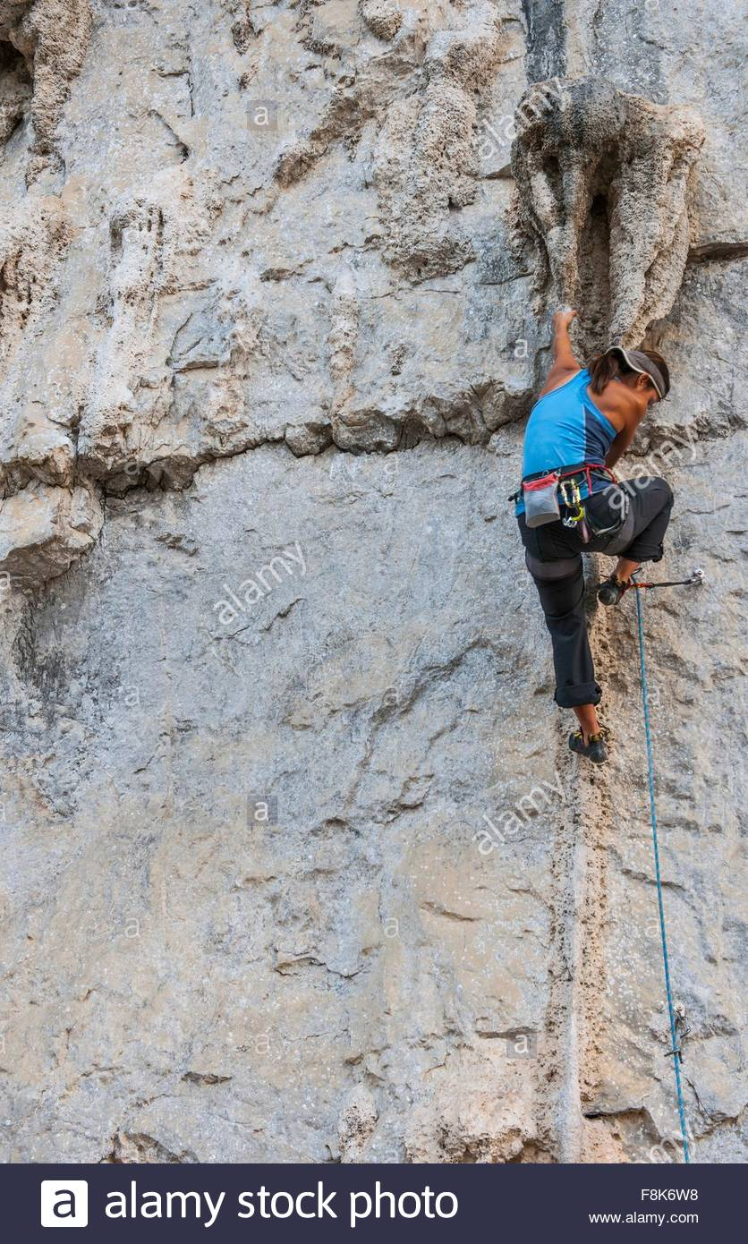 Female climber climbing on Riverside crag - a limestone cliff in Yangshuo, Guangxi Zhuang, China - Stock Image
