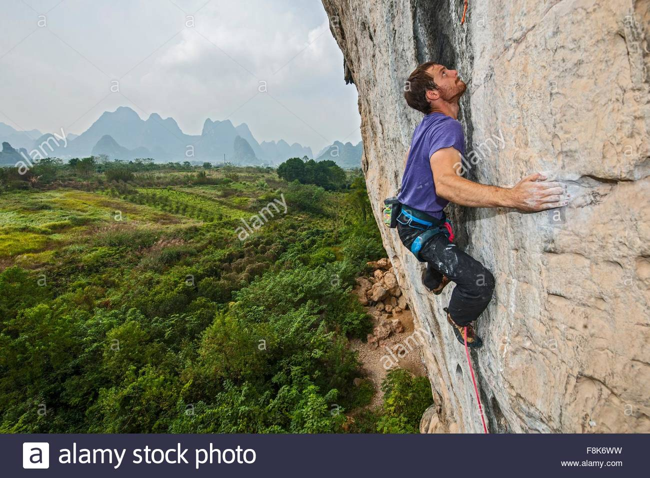 Elevated view of male climber climbing at white Mountain - a limestone cliff in Yangshuo, Guangxi Zhuang, China - Stock Image