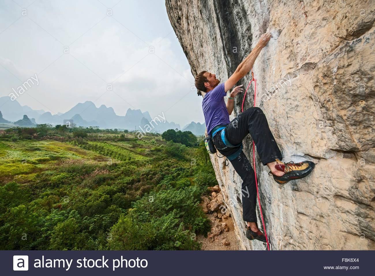 Male climber climbing at white Mountain - a limestone cliff in Yangshuo, Guangxi Zhuang, China - Stock Image