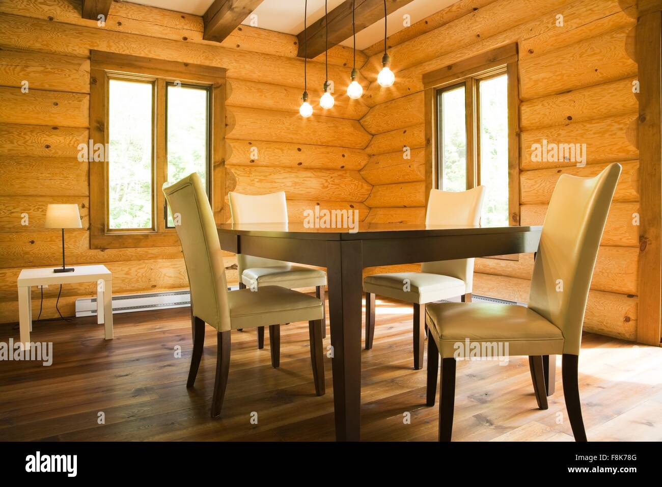 Dining table and chairs with modern lighting in Eastern white pine log cabin - Stock Image