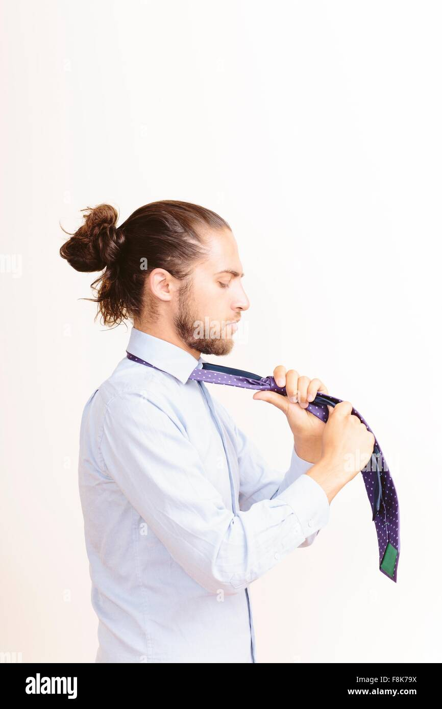 Young man with hair in bun, getting dressed, tying neck tie - Stock Image