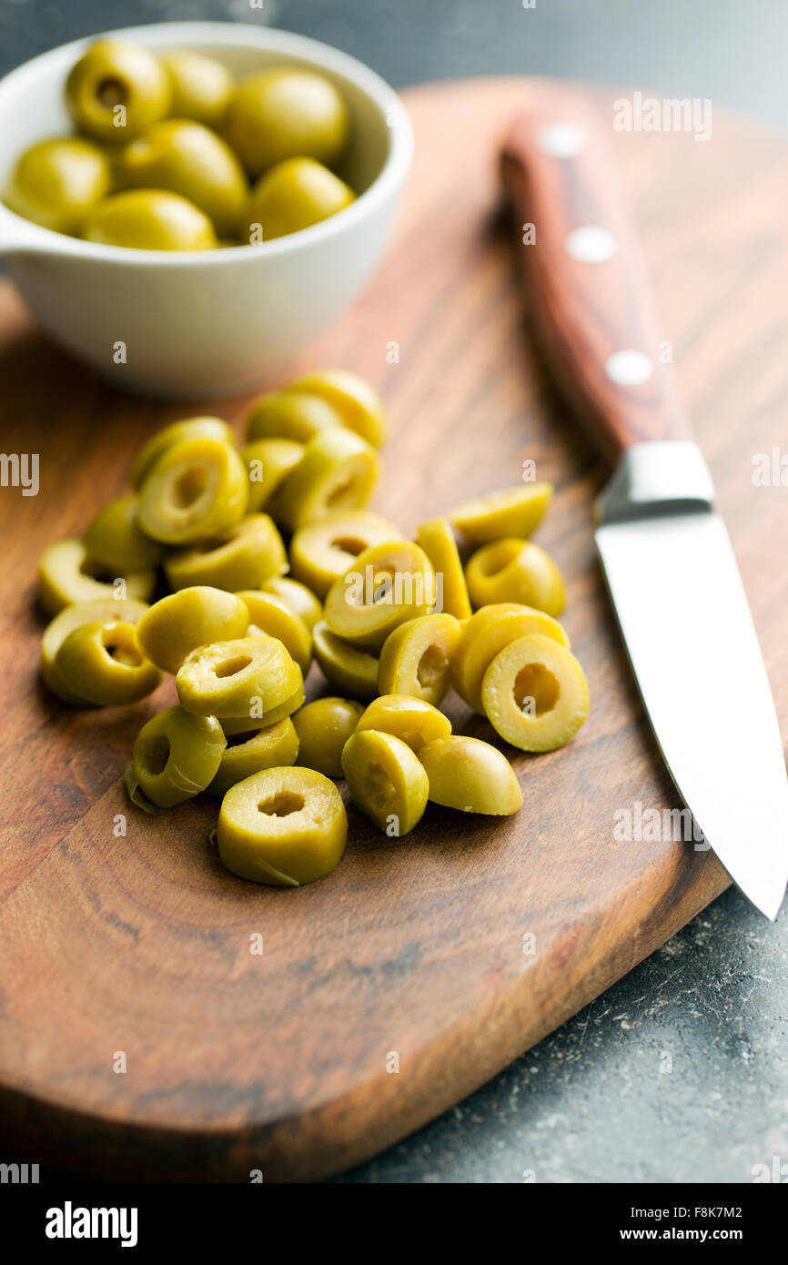 sliced green olives on cutting board - Stock Image