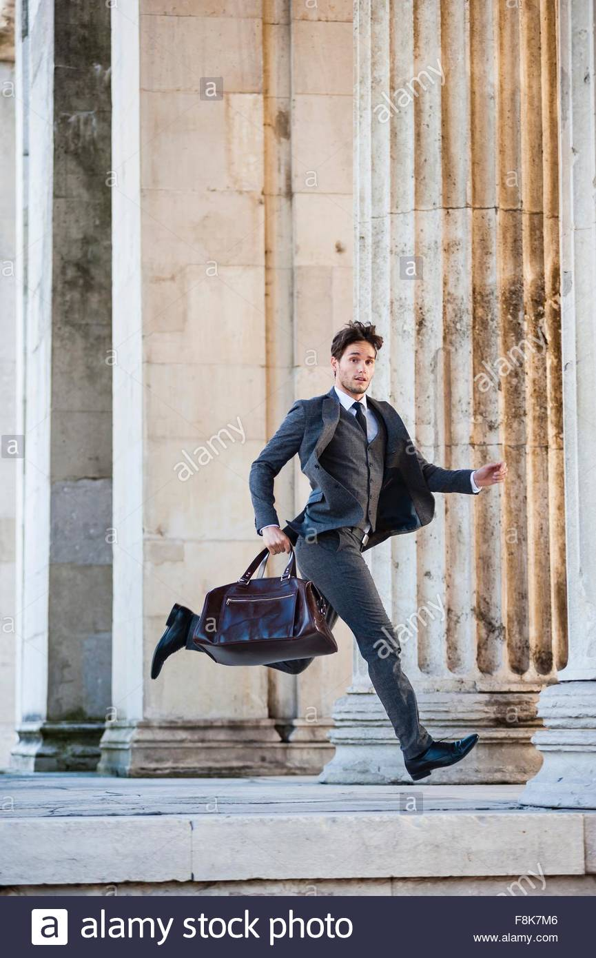 Side view of mid adult man wearing full suit carrying holdall running, in mid air, looking at camera - Stock Image