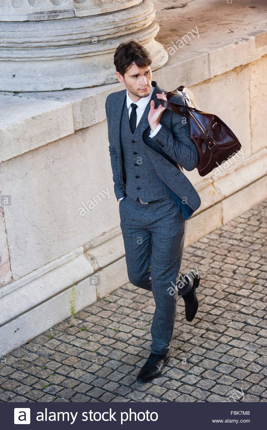 High angle view of mid adult man wearing full suit carrying bag over shoulder looking away - Stock Image