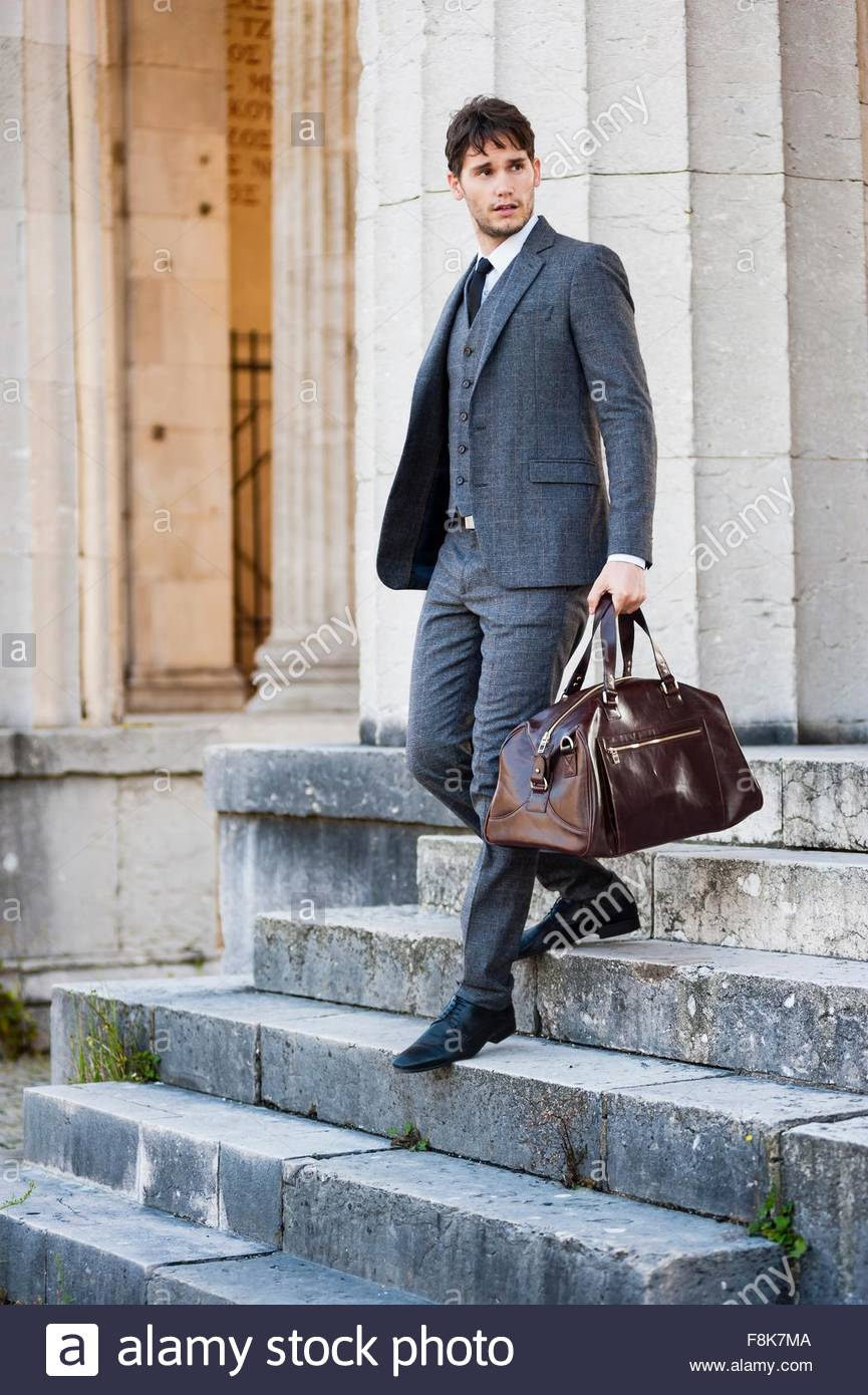 Mid adult man in full suit carrying holdall walking down steps, looking away - Stock Image