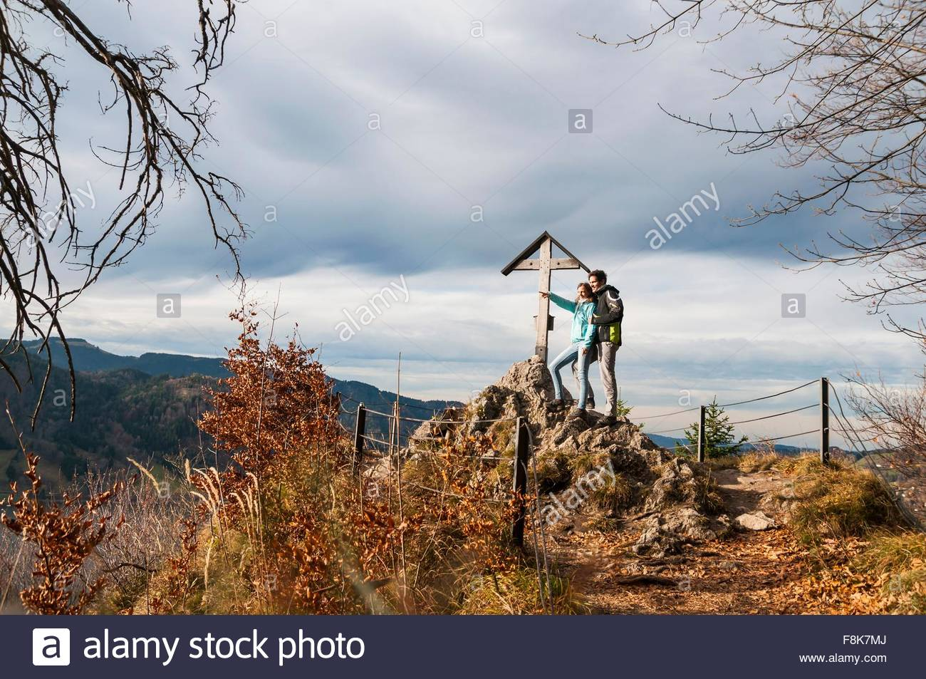 Couple by wood structure arms around each other looking at view pointing, Schliersee, Bavaria - Stock Image