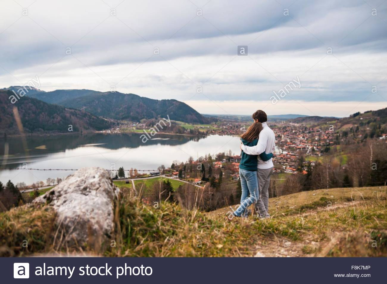 Rear view of couple arms around each other looking at view of lake, Schliersee, Bavaria - Stock Image