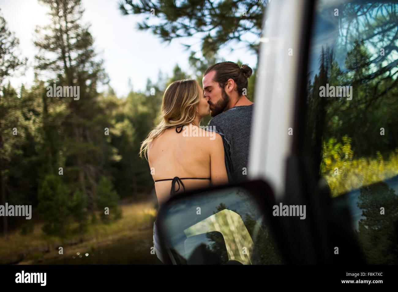 Rear view of romantic young couple kissing at riverside, Lake Tahoe, Nevada, USA - Stock Image