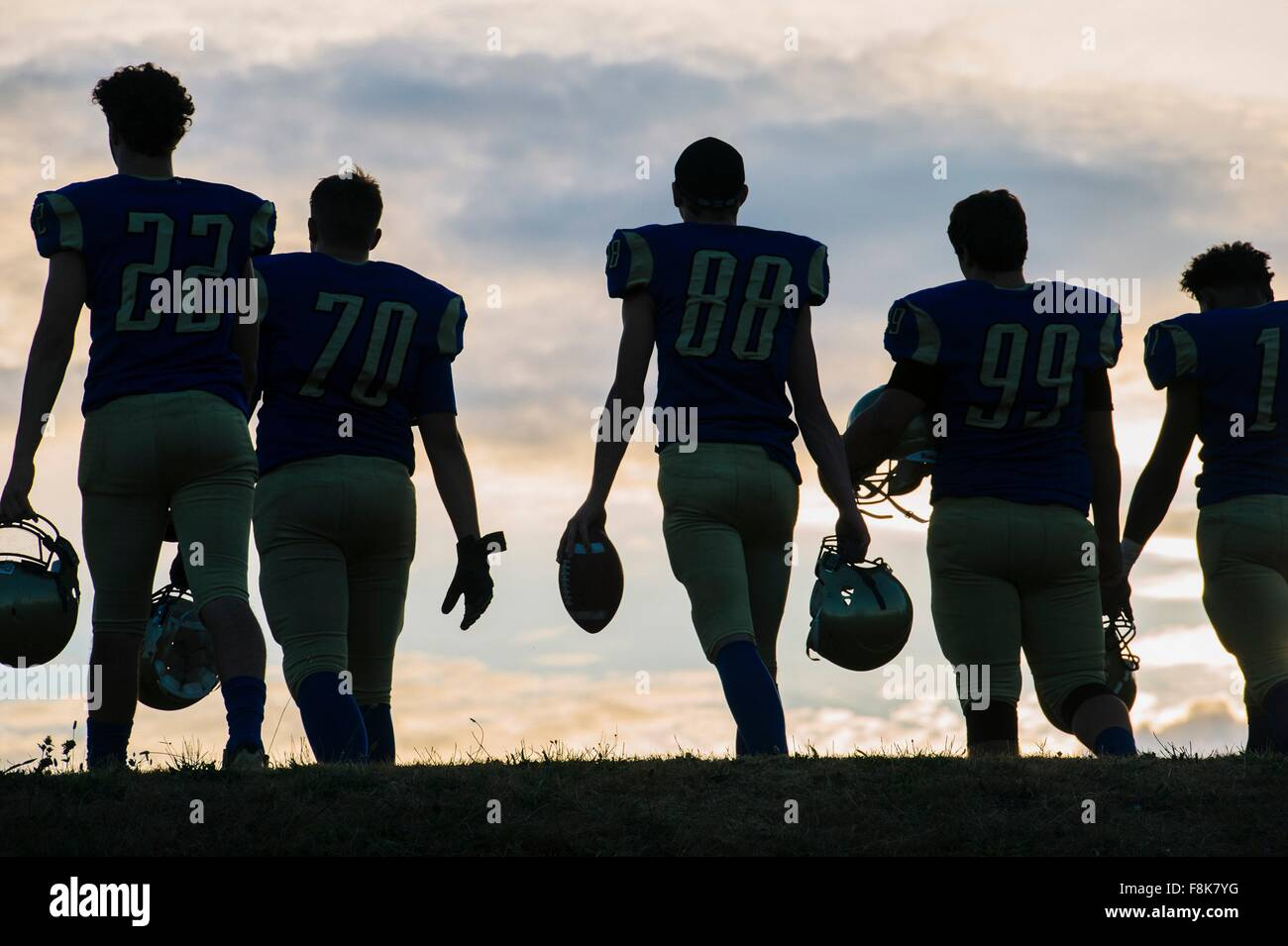 Group of young american football players walking away, rear view - Stock Image