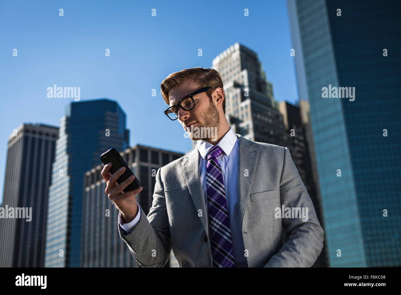 Young businessman in front of office building reading smartphone texts, New York, USA - Stock Image