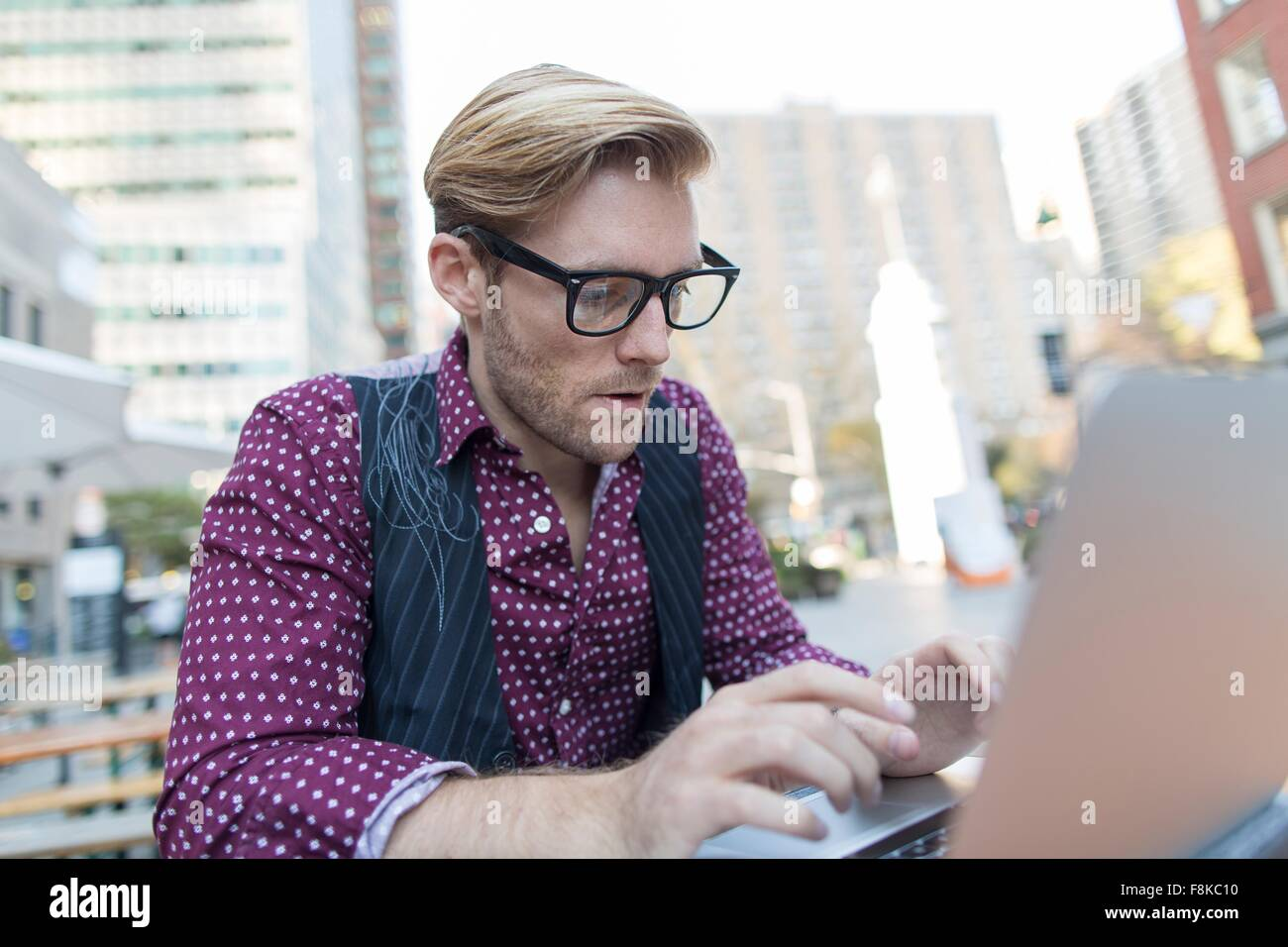 Stressed young businessman typing on laptop at sidewalk cafe, New York, USA - Stock Image