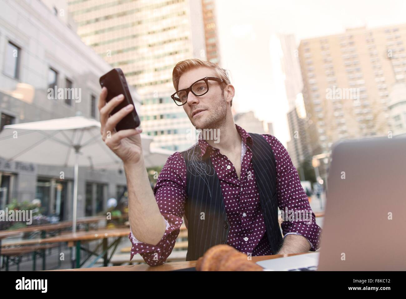 Stressed young businessman reading smartphone at sidewalk cafe, New York, USA - Stock Image