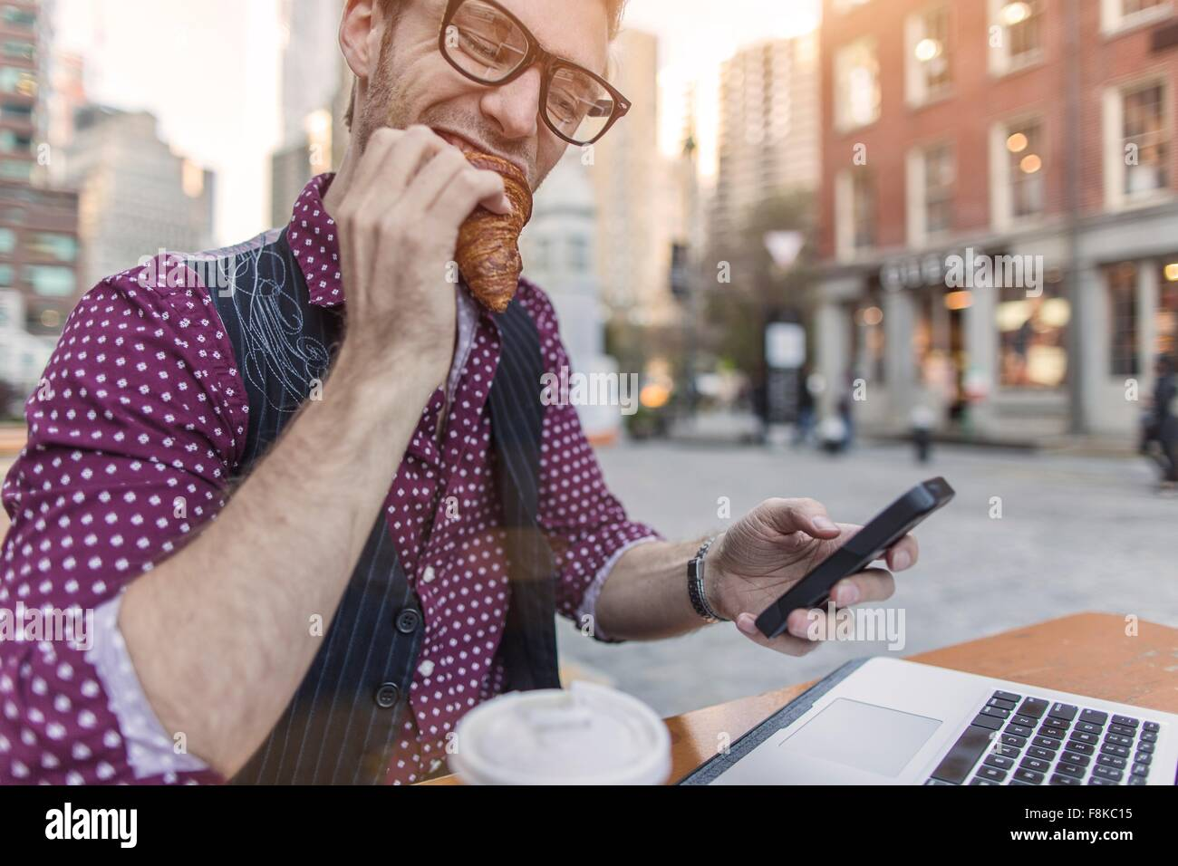 Stressed young businessman reading smartphone whilst eating at sidewalk cafe, New York, USA - Stock Image
