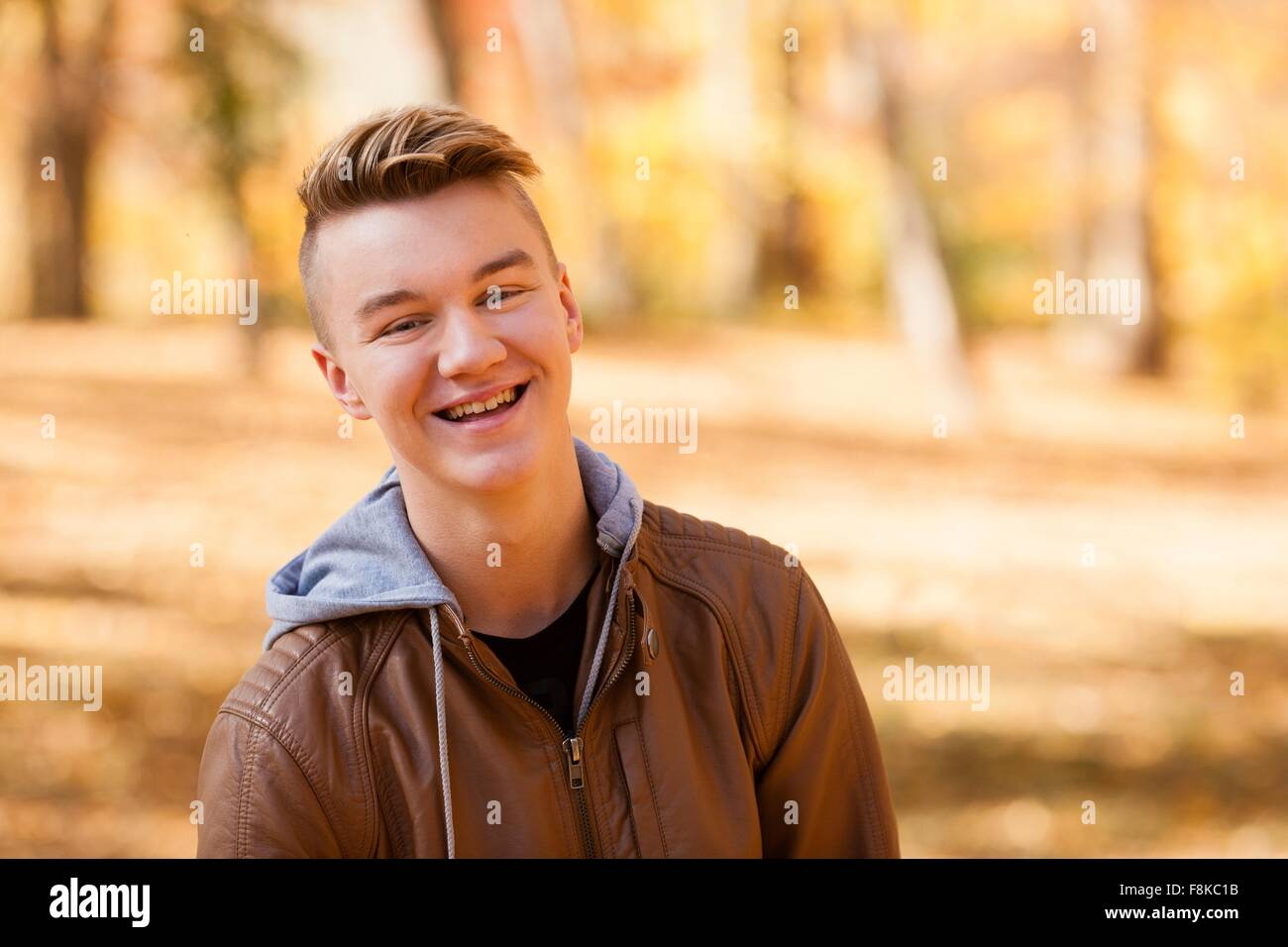 Head and shoulder portrait of teenage boy wearing leather jacket in autumn forest Stock Photo