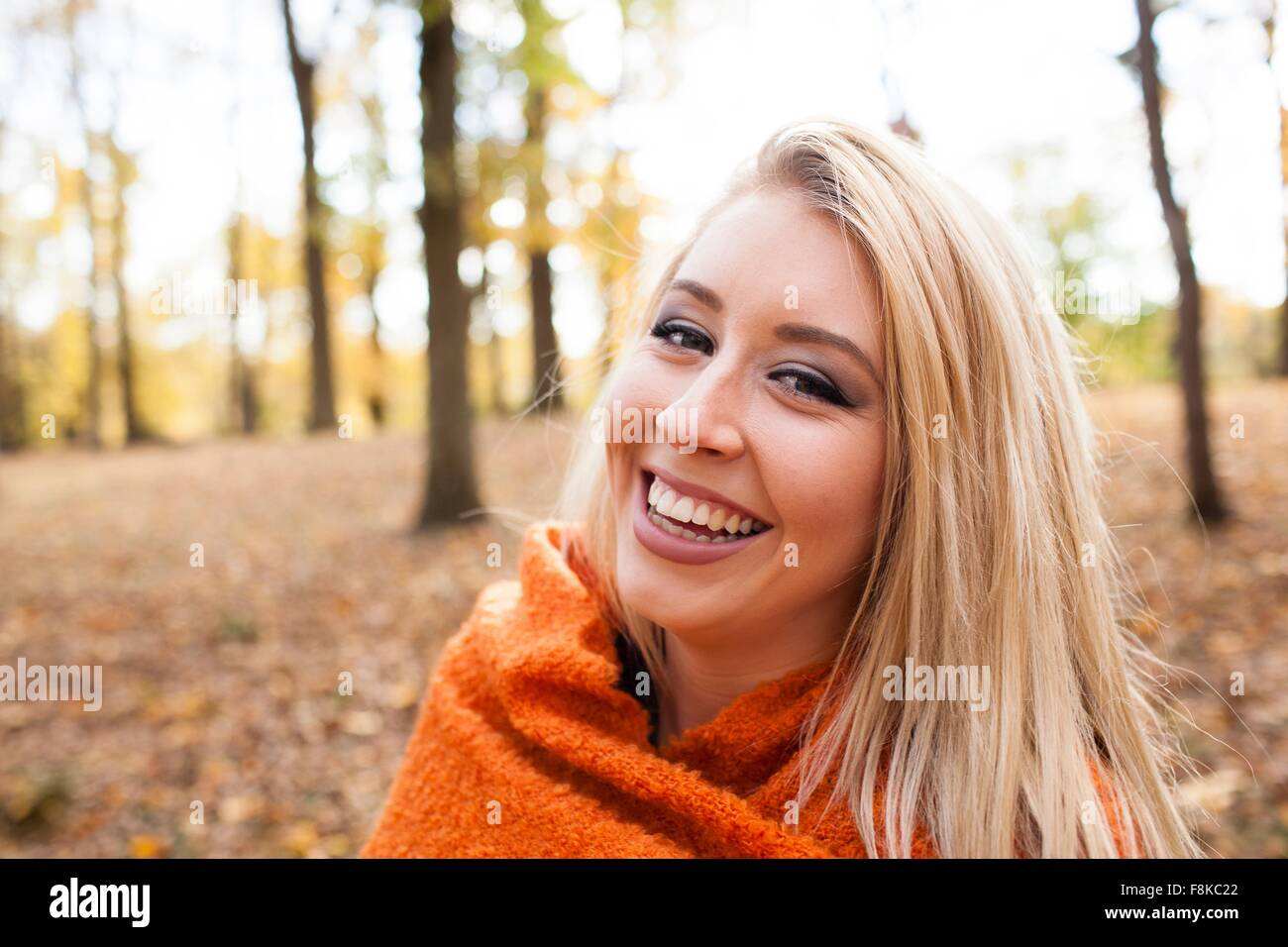 Portrait of young woman with long blond hair wrapped in blanket in autumn forest - Stock Image