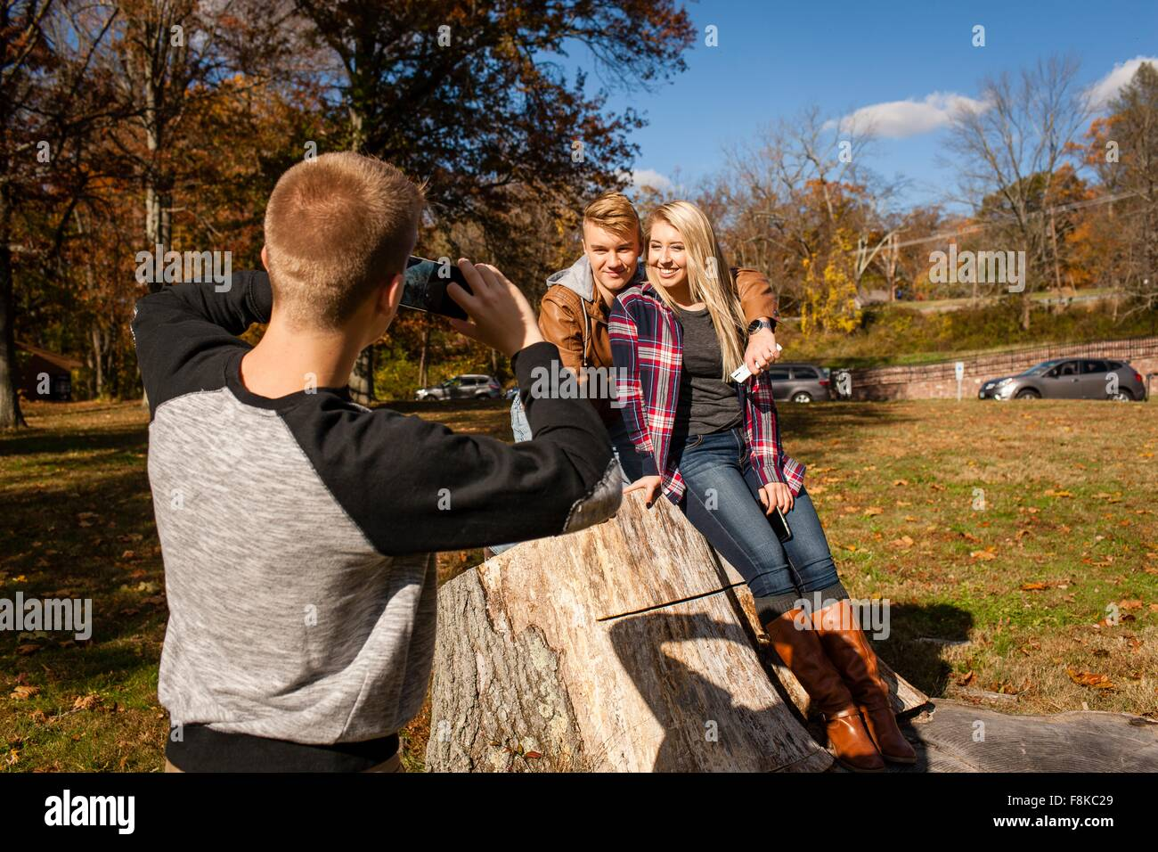 Teenage boy photographing brother and adult sister in autumn park - Stock Image