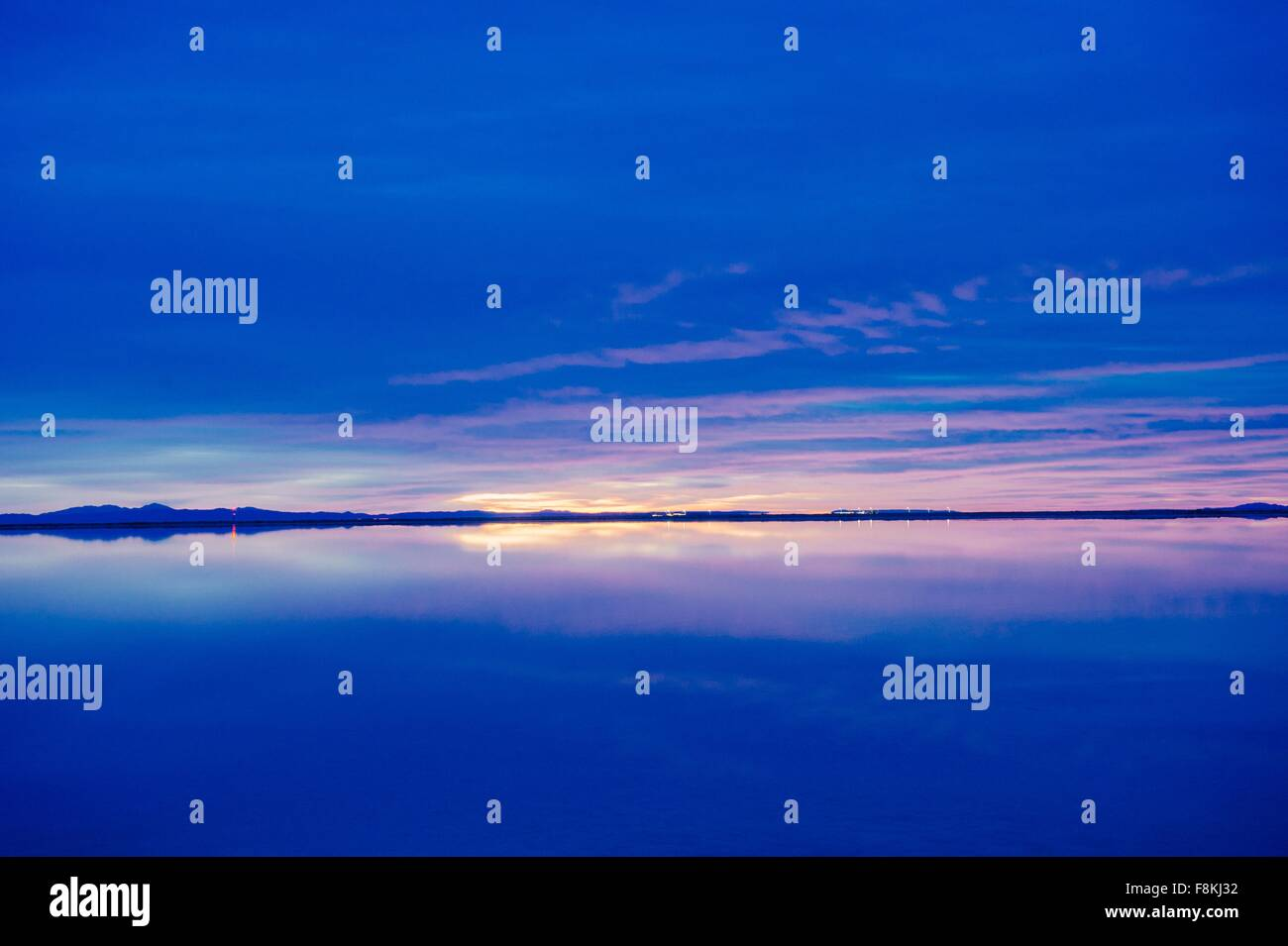 Reflection pool of horizon over water, blue evening sky and sunset, Bonneville, Utah, USA - Stock Image