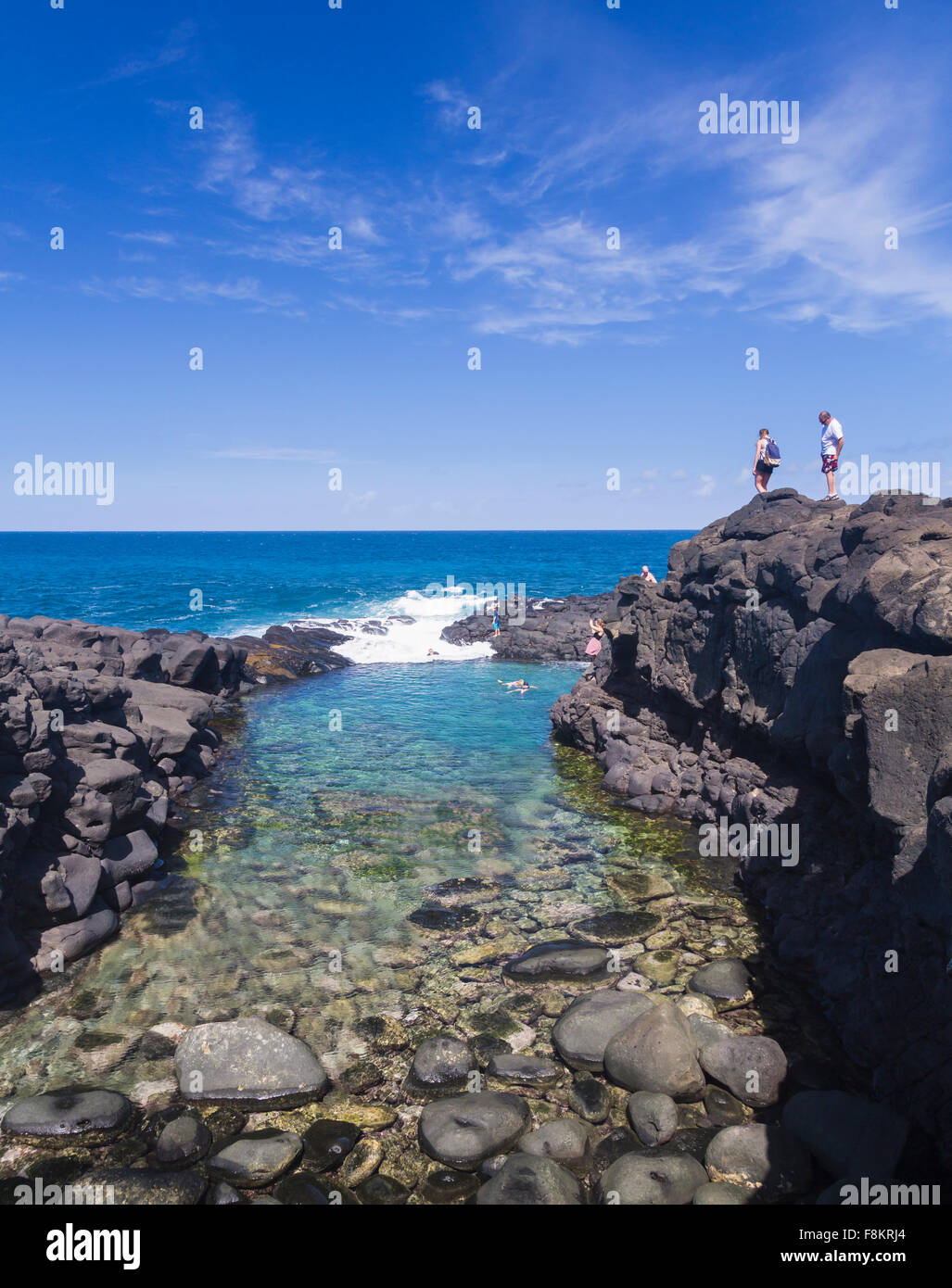 Tourists overlook snorkeling swimmers in the sea at Queens Bath tide pool near Princeville, Kauai - Stock Image
