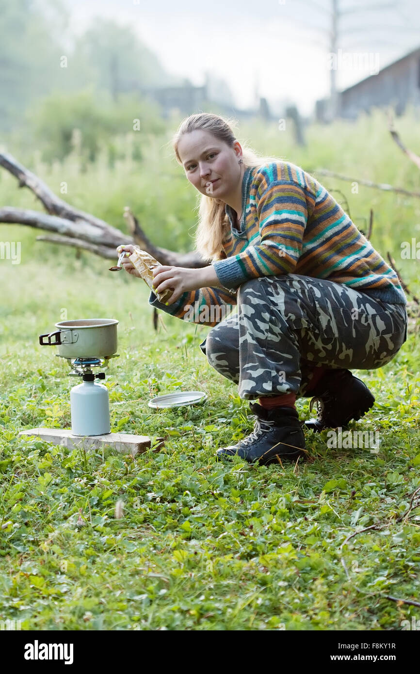 Girl making  coffee on gas burner at mountains - Stock Image