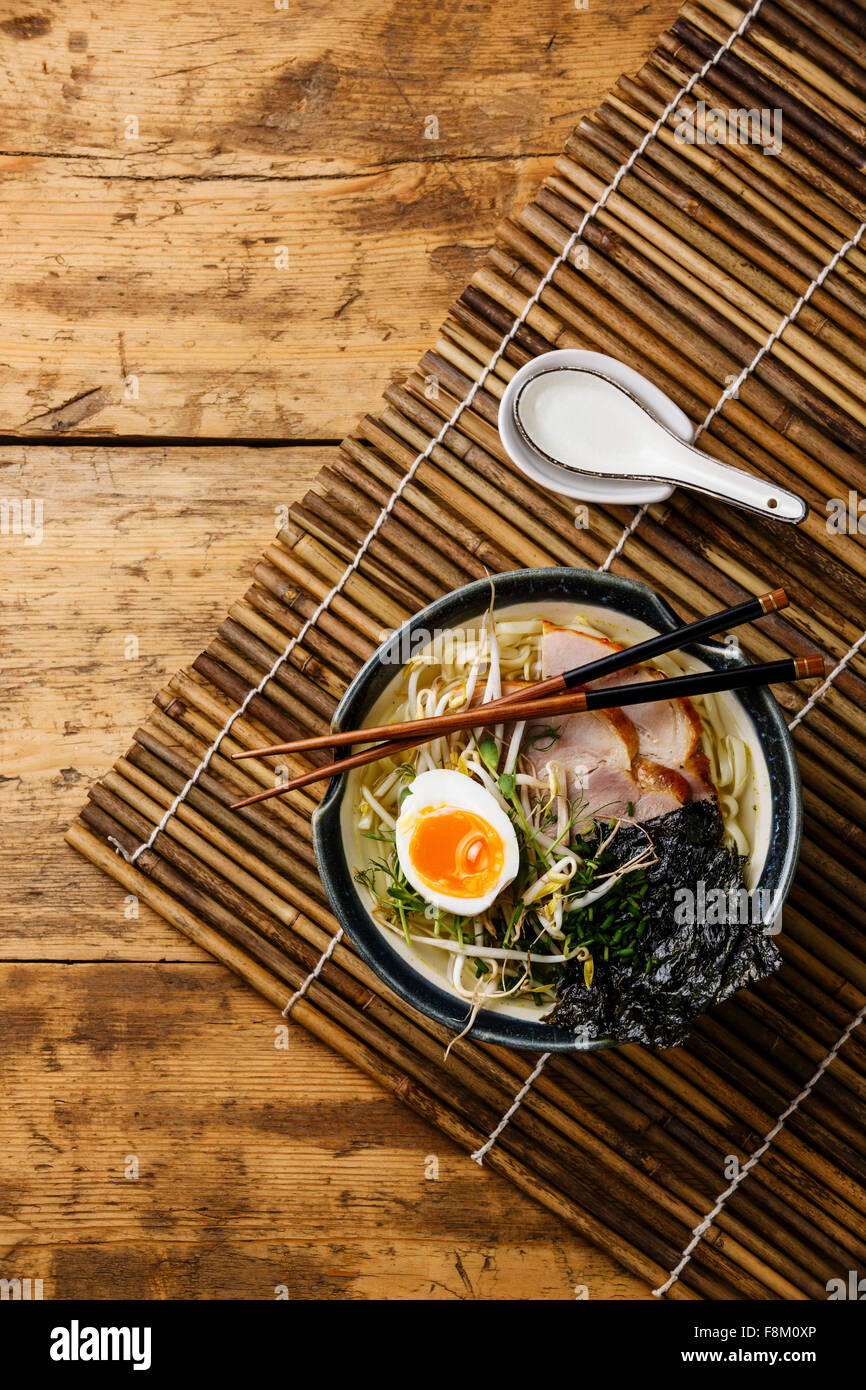 Udon noodle with boiled pork, wheat germ and egg on wooden background - Stock Image
