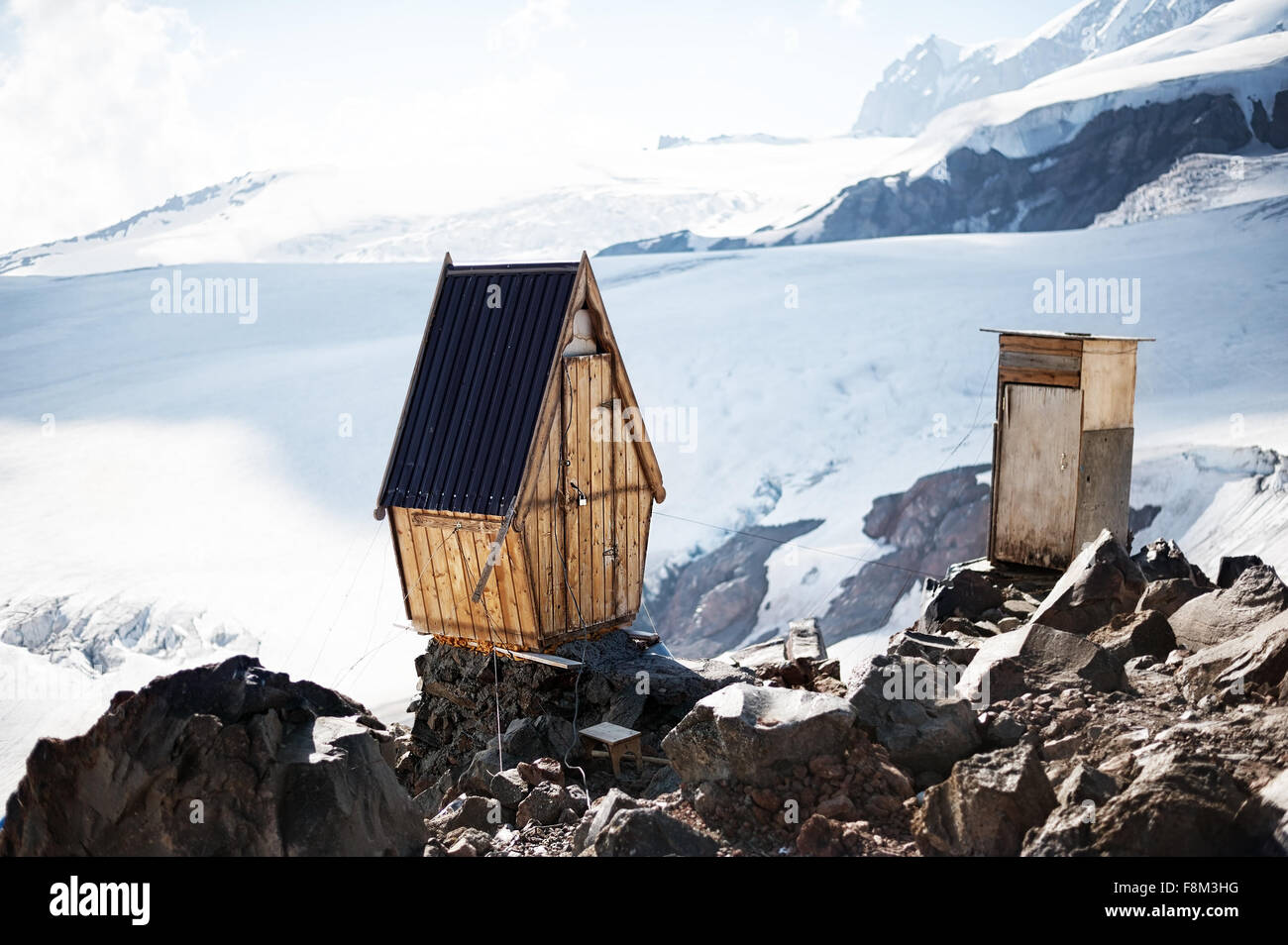 Old wooden toilets (WC) for climbers about break on edge of the cliff on permafrost glaciers on Elbrus mountain - Stock Image