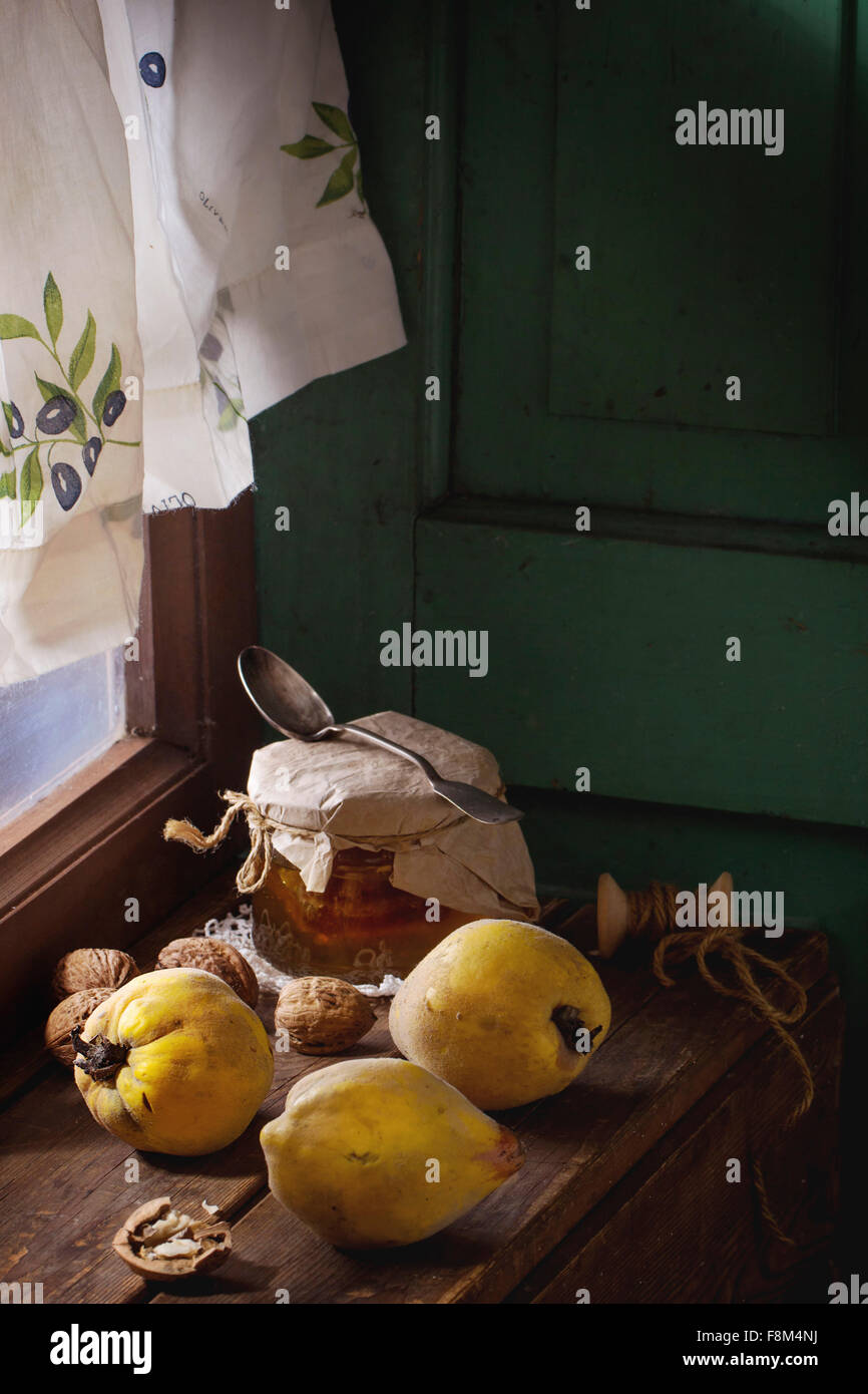 Three juicy quinces, walnuts and jar of honey over wooden table near window with bright sunlight. With green wooden - Stock Image