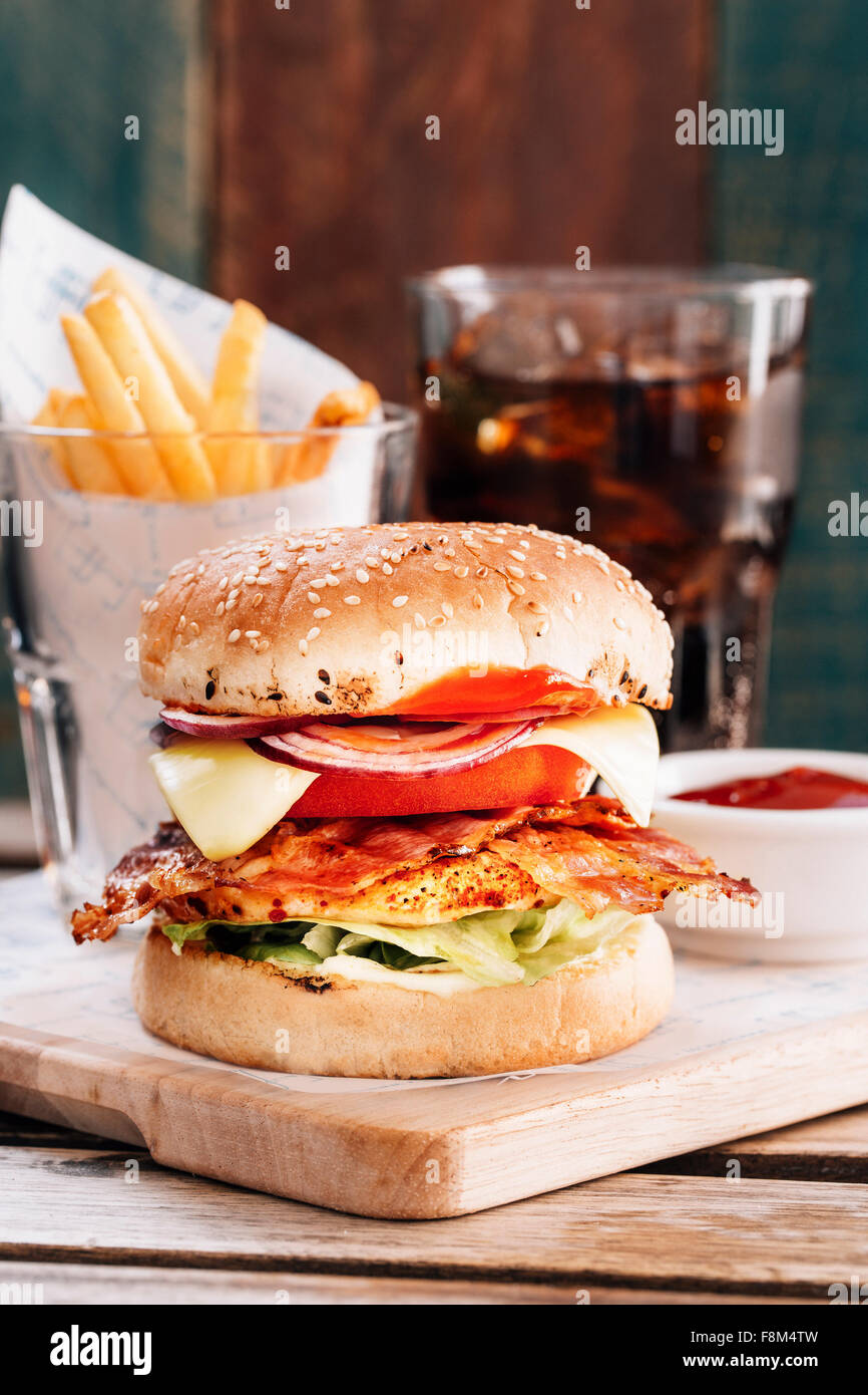 Chicken burger with bacon and glass of cola - Stock Image