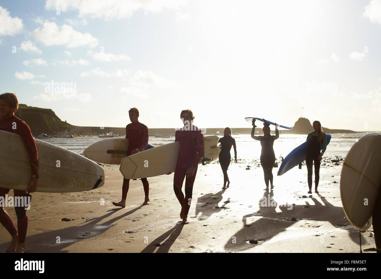 Group of surfers, walking on beach, carrying surfboards - Stock Image