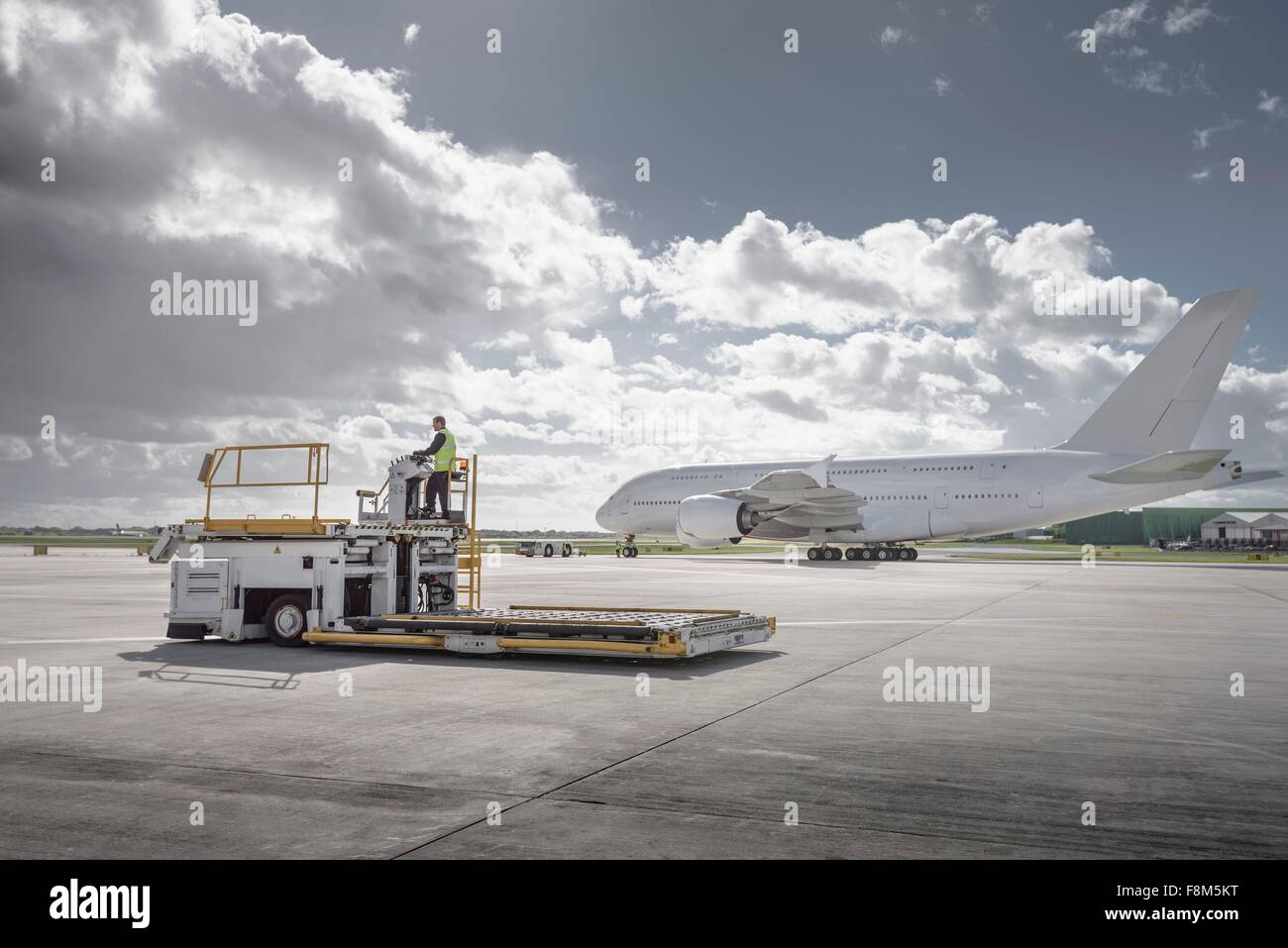 Freight handling machine with A380 aircraft on runway - Stock Image