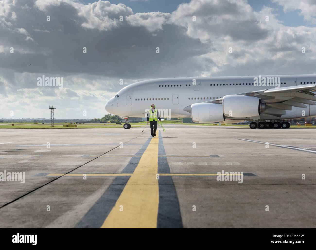 Chief engineer walking from runway as A380 aircraft departs from airport - Stock Image