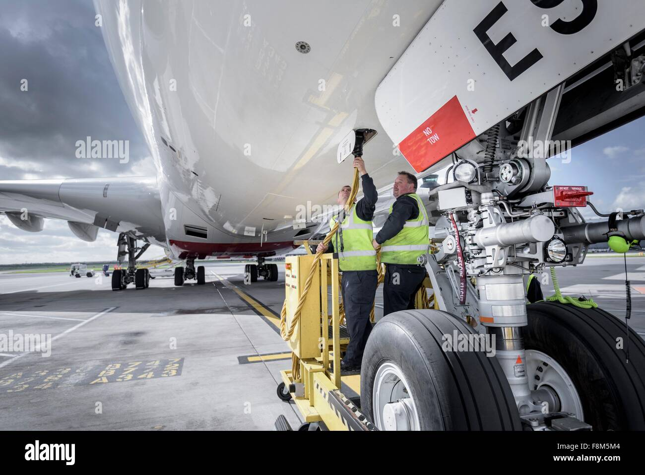 Ground crew operating loading equipment on A380 aircraft - Stock Image