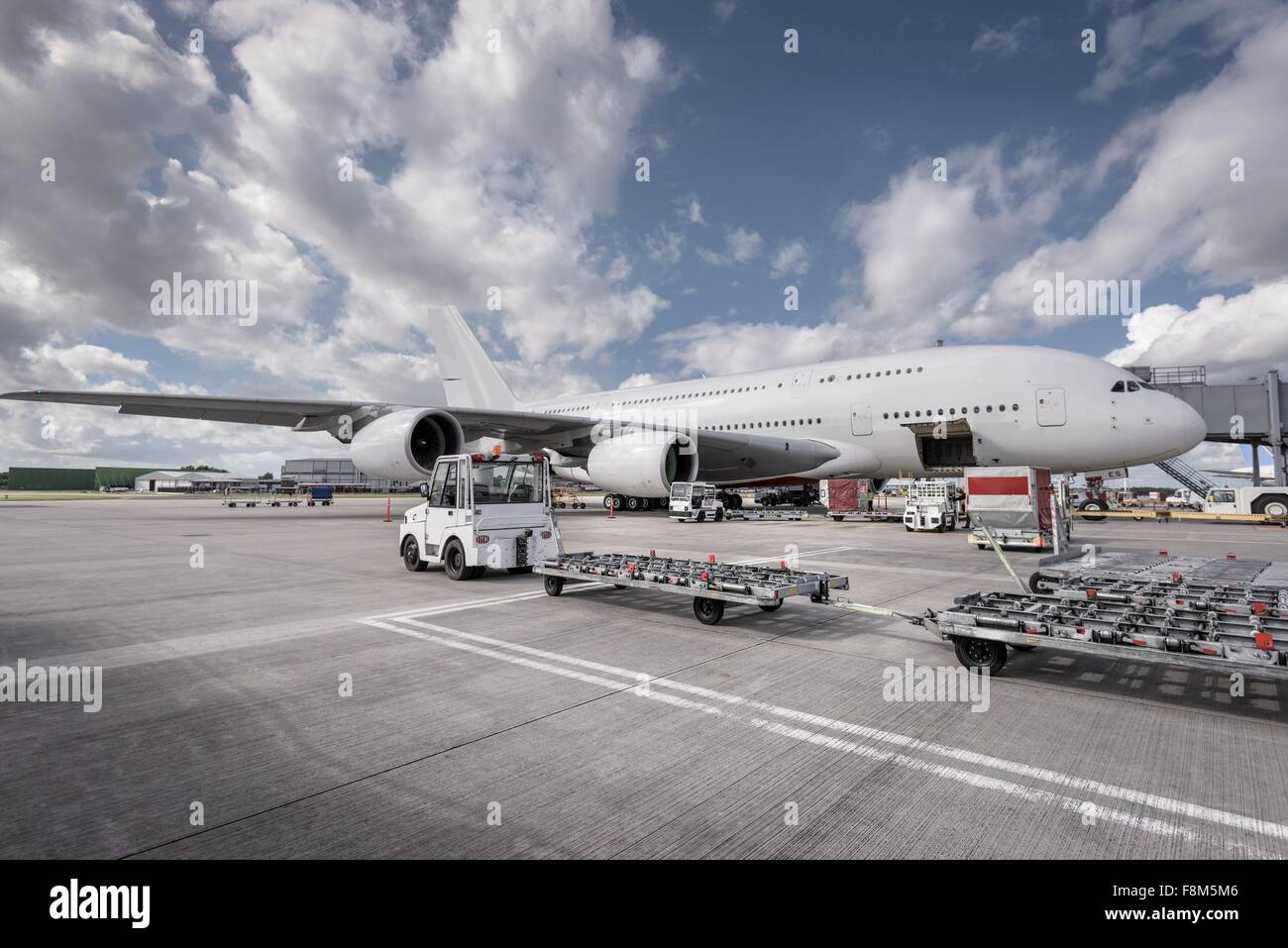 Ground crew loading A380 aircraft at airport - Stock Image