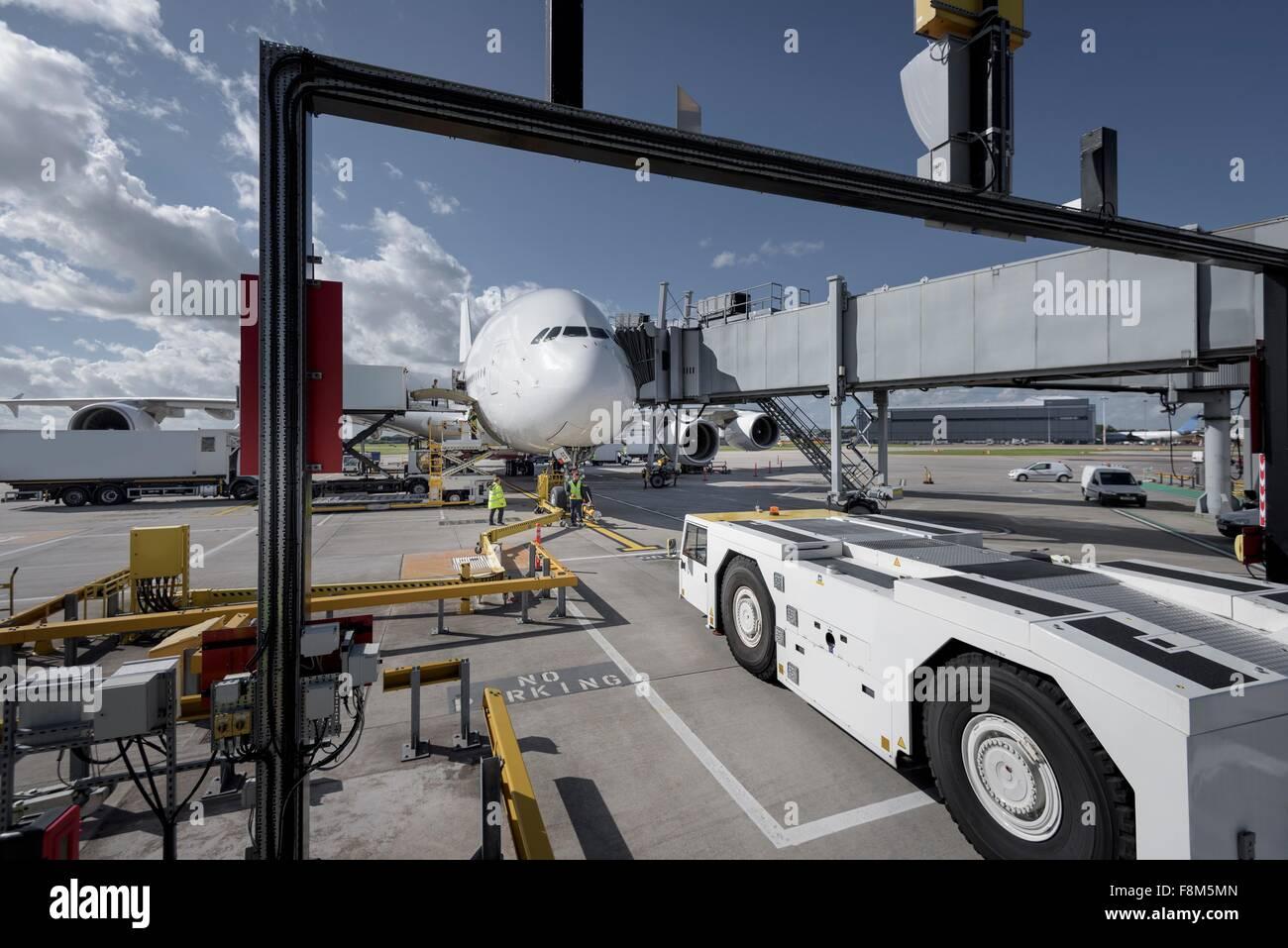 A380 aircraft and tug at stand at airport - Stock Image