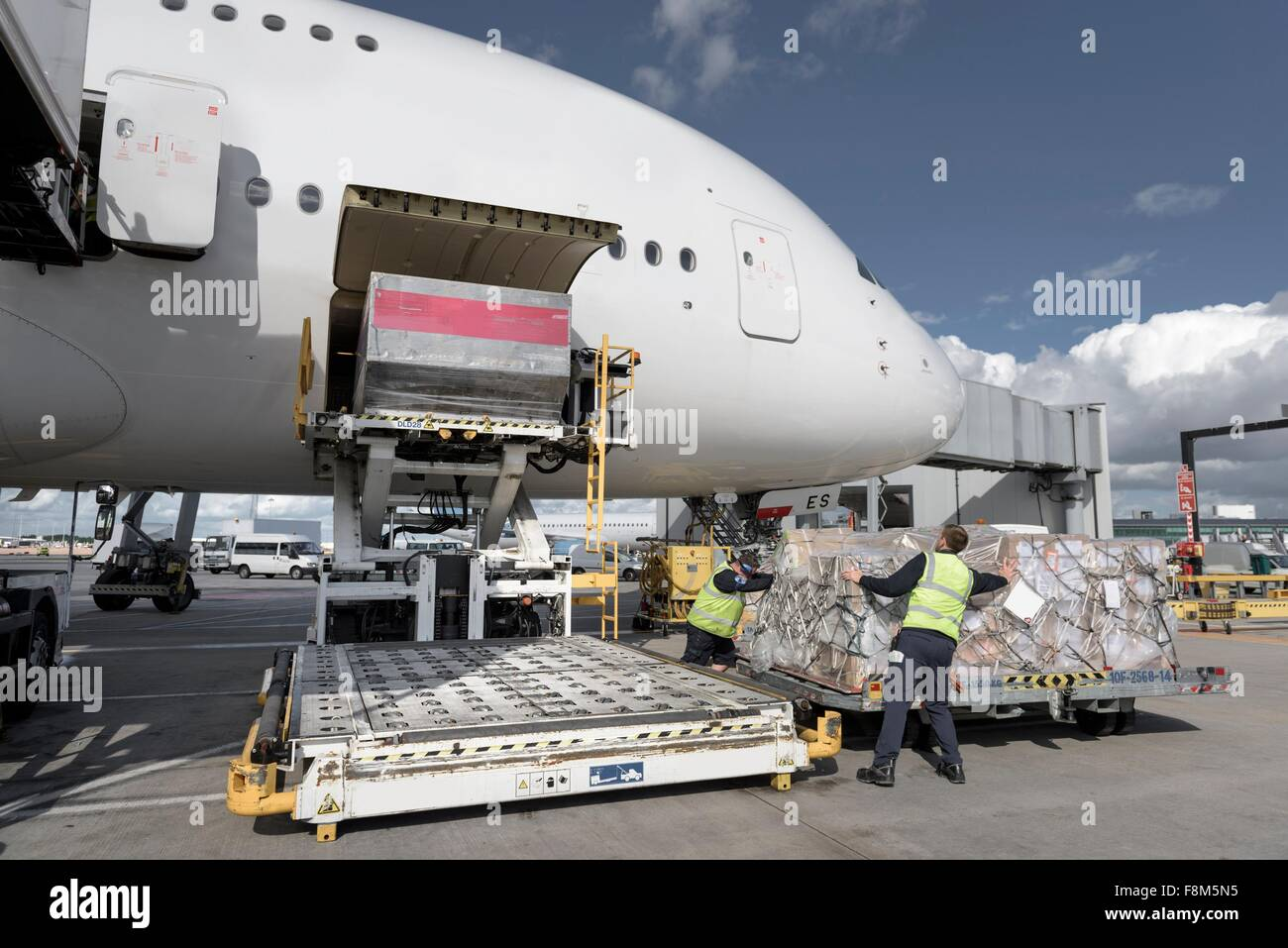 Ground crew loading freight into A380 aircraft - Stock Image