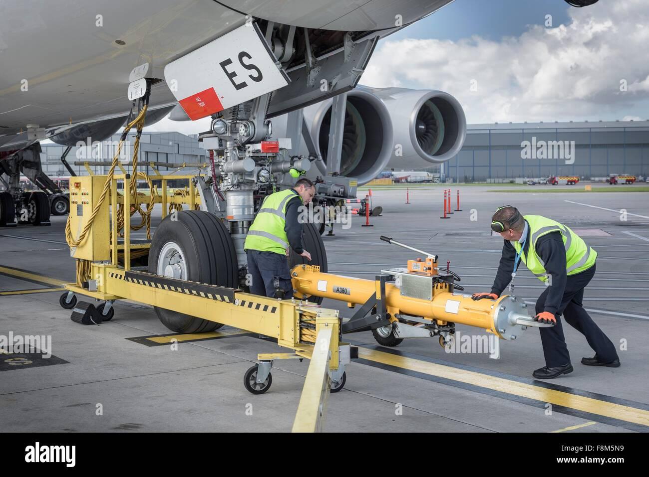 Ground crew fixing tow bar onto A380 aircraft at airport - Stock Image